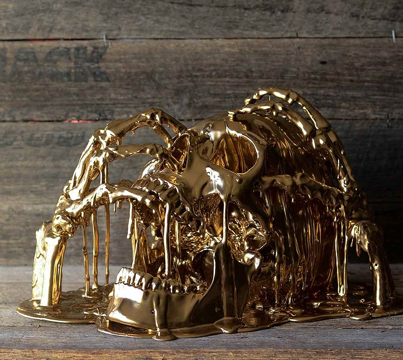 gold melting skull with hands